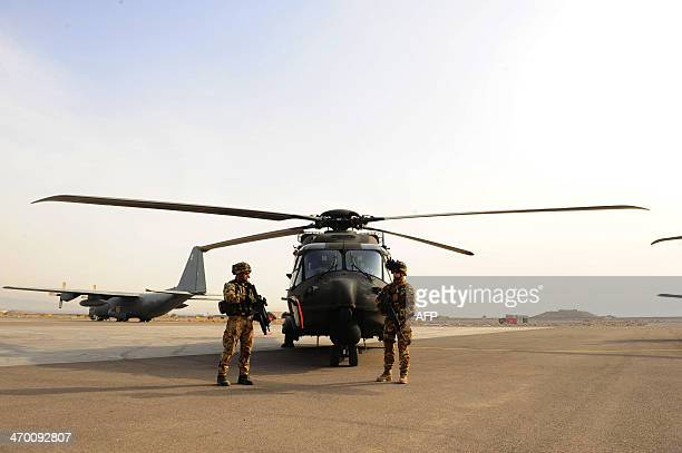 Italian soldiers stand guard during a change of command ceremony at an Italian military camp near Herat airport on February 18 2014 The commander of...