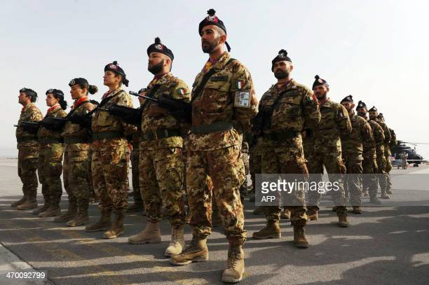 Italian soldiers stand to attention during a change of command ceremony at an Italian military camp near Herat airport on February 18 2014 The...