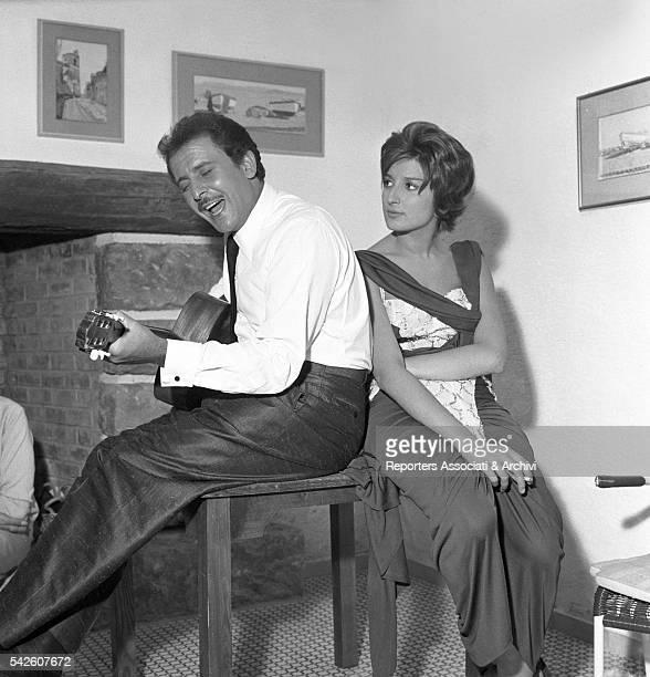 Italian songwriter Domenico Modugno playing a guitar next to Italian singer Mina during a break on the set of Appuntamento a Ischia 1960