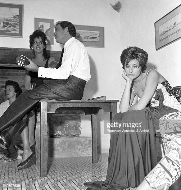 Italian songwriter Domenico Modugno playing a guitar under the gaze of Italian actress Antonella Lualdi on the set ofAppuntamento a Ischia Italian...