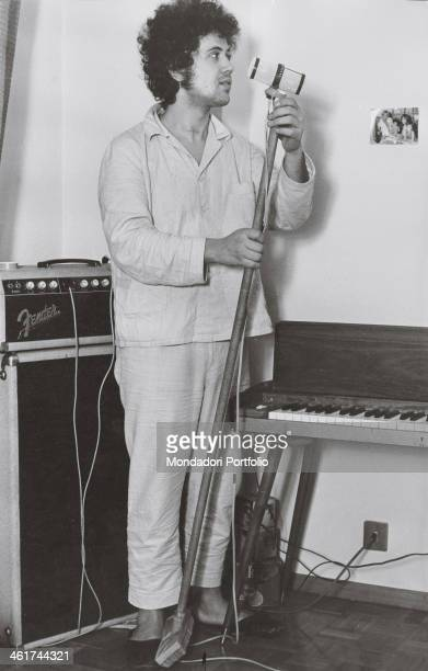Italian songwriter Lucio Battisti in pajamas and slippers near some music equipments mimicking jokingly a performance leaning the microphone on a...