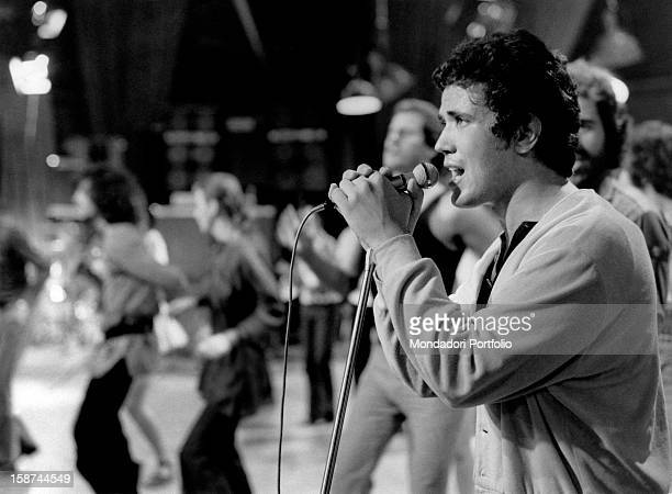 Italian songwriter Lucio Battisti performs singing in the middle of a TV studio surrounded by young men and women dancing Rome August 1971