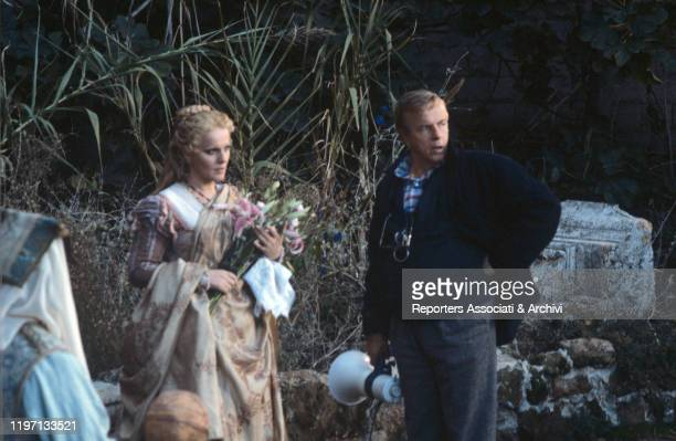 Italian soprano Katia Ricciarelli as Desdemona holding a bunch of flowers beside Italian director Franco Zeffirelli on the set of the film Otello....