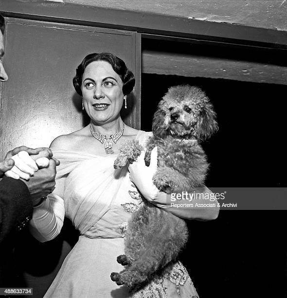 Italian soprano Renata Tebaldi holding her dog while being congratulated in the backstage after her concert at Sistina theatre Rome