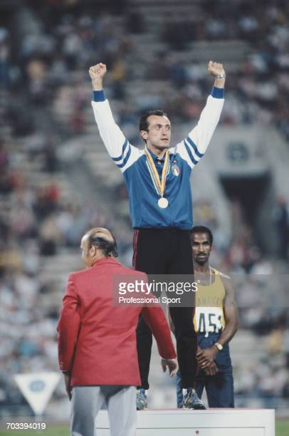Italian sprint athlete Pietro Mennea of the Italy team raises his arms in the air on the medal podium after finishing in first place to win the gold...