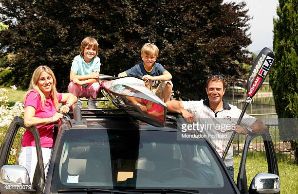 Italian sprint canoer Antonio Rossi his wife Lucia and their children Riccardo and Angelica pose around the car carrying the canoe for training near...