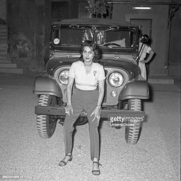Italian stage and film actress Anna Magnani poses in front of a jeep at 'Palazzo Altieri' Rome 1957