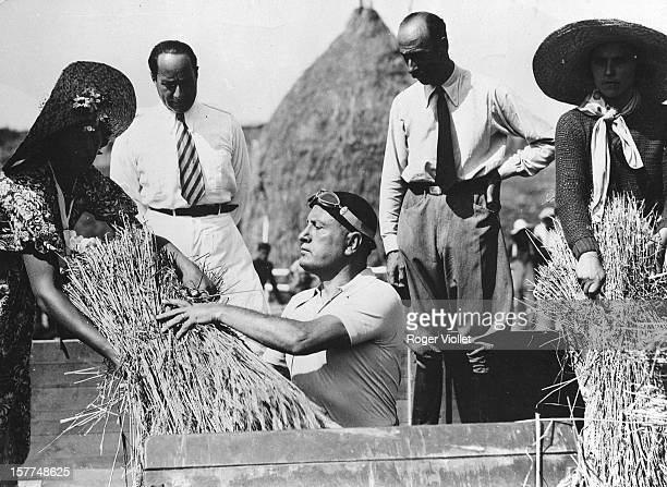Italian statesman Benito Mussolini with farmers taking part in the first threshing of the wheat in Littoria a city created in the Pontine Marshes...
