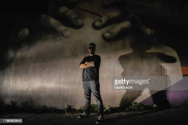 Italian Street Artist Ligama poses for a photo near his mural 'Quando manca l'aria' to celebrate the love between artists Amedeo Modigliani and...