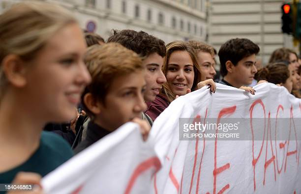 Italian students hold a banner during a demonstration against education cuts in downtown Rome on October 11 2013 AFP PHOTO / Filippo MONTEFORTE