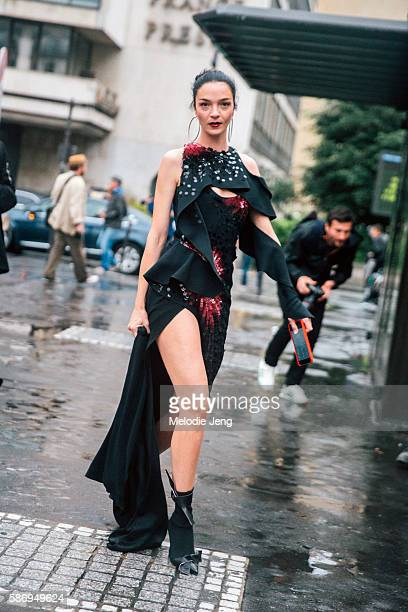 Italian supermodel Mariacarla Boscono wears an asymmetrical red and black draped and embellished Atelier Versace Fall/Winter 2016 couture dress and...