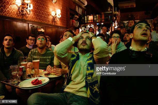 TOPSHOT Italian supporters react as they watch in a bar the FIFA World Cup 2018 qualification football match between Italy and Sweden on November 13...