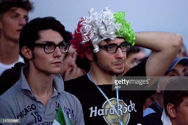 Italian supporters react in front of a giant screen during the final of the Euro 2012 tournament opposing Italy to Spain on July 1, 2012 on a sea...