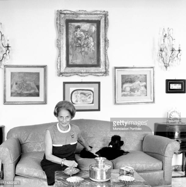 Italian tailor Maria Antonelli petting a dog sitting on the sofa 1960s