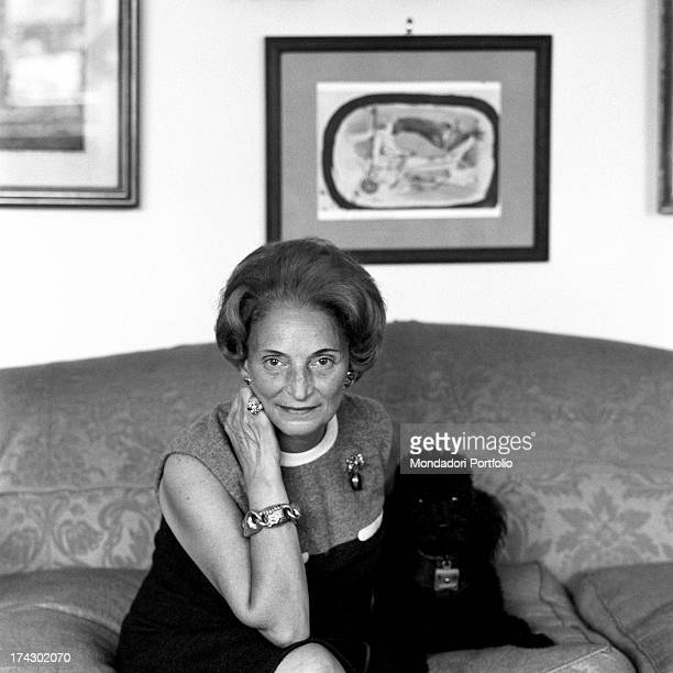 Italian tailor Maria Antonelli posing sitting on the sofa beside a dog 1960s