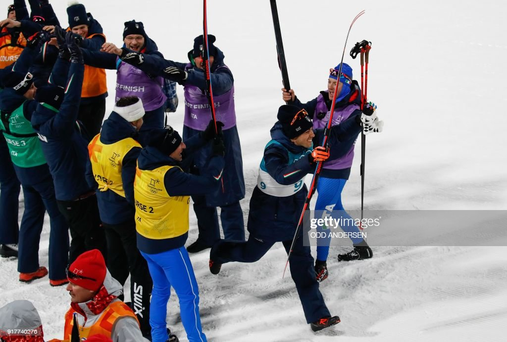 TOPSHOT - Italian team members form an honour guard as they celebrate Italy's Federico Pellegrino second place silver medal win in the men's cross-country individual sprint classic final at the Alpensia cross country ski centre during the Pyeongchang 2018 Winter Olympic Games on February 13, 2018 in Pyeongchang. / AFP PHOTO / Odd ANDERSEN