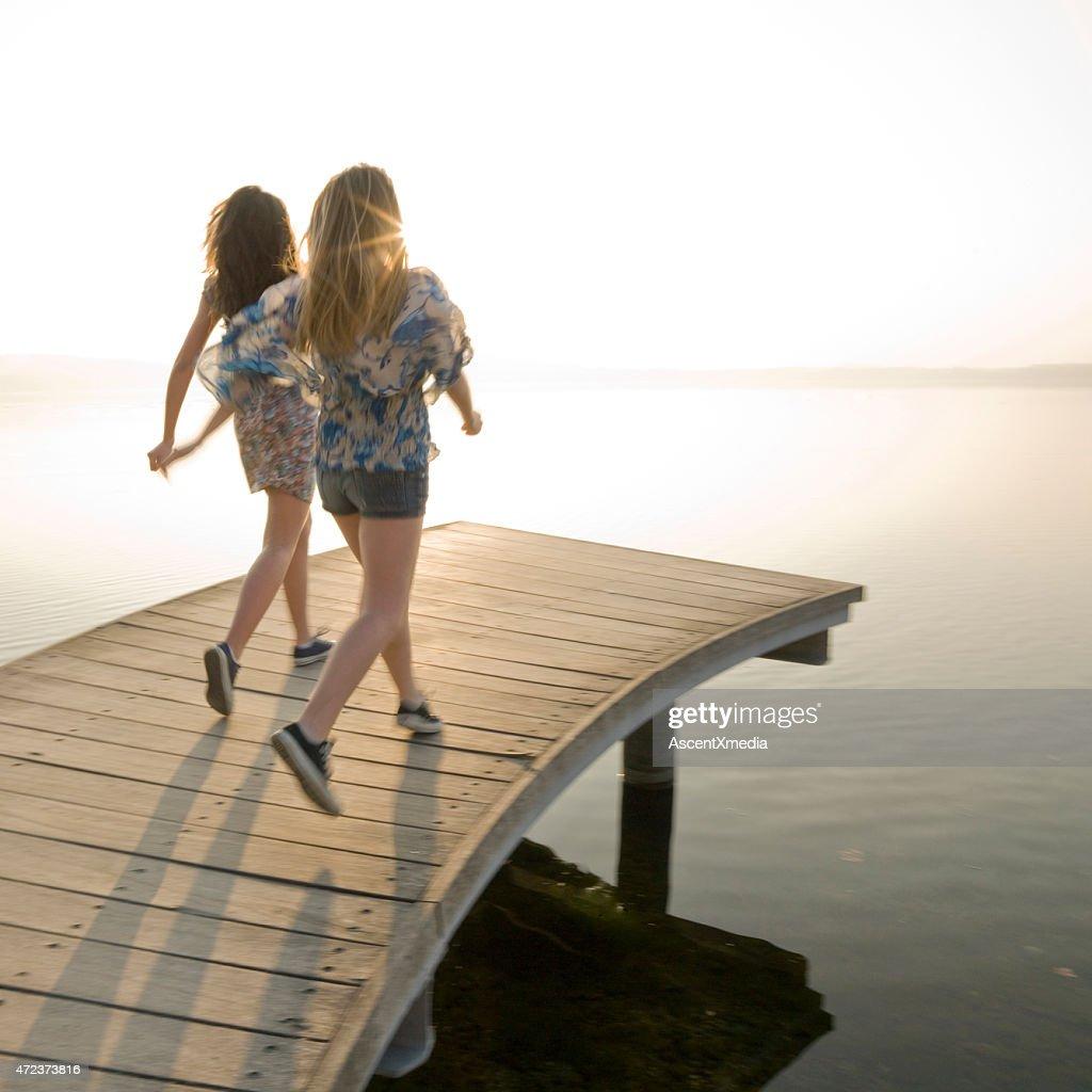 Italian Teenage Girls Walk Along Wooden Pier By Lake Stock Photo