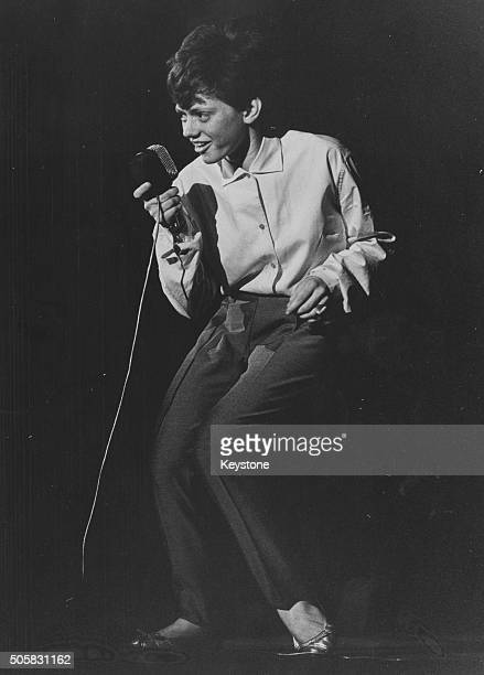 Italian teenage singer Rita Pavone wearing trousers and shirt a she performs on stage in Milan June 1st 1963