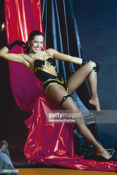 Italian television host and actress Barbara D'Urso posing smiling for a photo shoot wearing a stage costume nylon stockings and black gloves Italy...