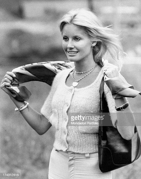 Italian television presenter and actress Gabriella Farinon adjusting a scarf on her shoulders 1970s