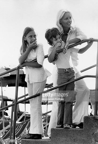Italian television presenter and actress Gabriella Farinon and her children Barbara and Francesco Modesti leaning on a handrail Gaeta 1970s