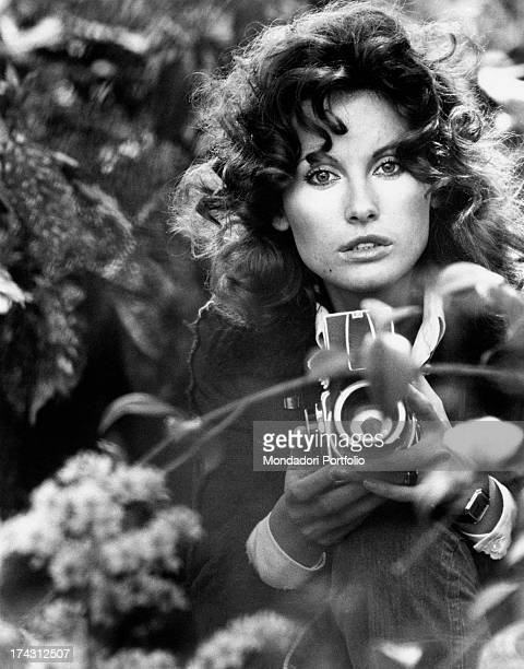 Italian television presenter and actress Gabriella Farinon in a glasshouse holding a camera in her hands Rome 1970s