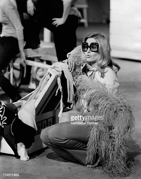 Italian television presenter and actress Gabriella Farinon kneeling on the set of the TV broadcast Mai di sabato signora Lisistrata Rome 1971