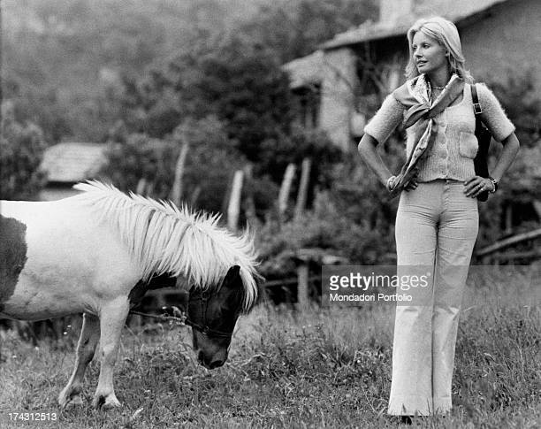 Italian television presenter and actress Gabriella Farinon near a pony holding her hands on her hips 1970s