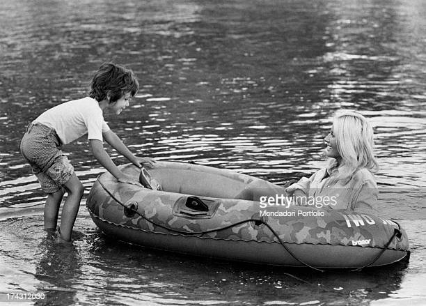 Italian television presenter and actress Gabriella Farinon sitting in a dinghy playing with her son Francesco Modesti Gaeta 1970s