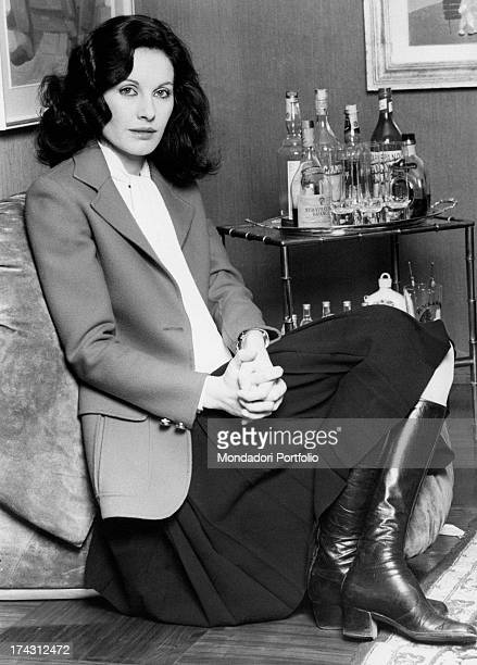 Italian television presenter and actress Gabriella Farinon sitting in a chair with woven hands Milan 1970s