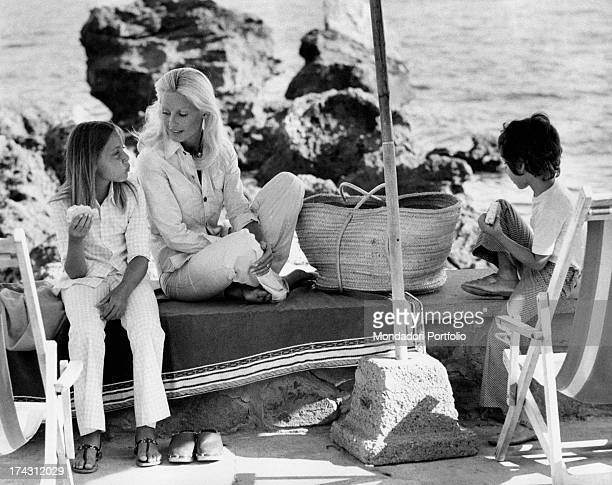 Italian television presenter and actress Gabriella Farinon sitting on a low wall and talking to her children Barbara and Francesco Modesti while they...