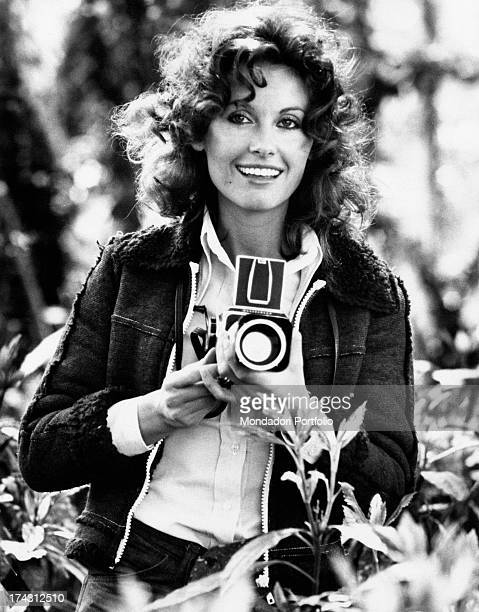 Italian television presenter and actress Gabriella Farinon smiling in a garden with a camera in her hands Rome 1970s