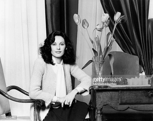 Italian television presenter and actress Gabriella Farinon smiling sitting beside a pot of tulips Milan 1970s