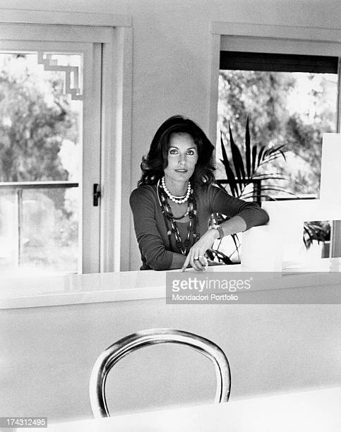 Italian television presenter and actress Gabriella Farinon smiling leaning on a piece of furniture Rome 1970s