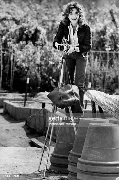 Italian television presenter and actress Gabriella Farinon standing on a flowerpot fixing a camera on a tripod Rome 1970s