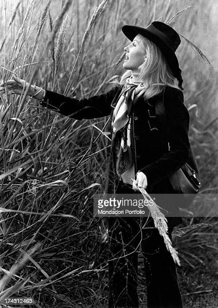 Italian television presenter and actress Gabriella Farinon walking in a field picking some flowers Rome 1970s