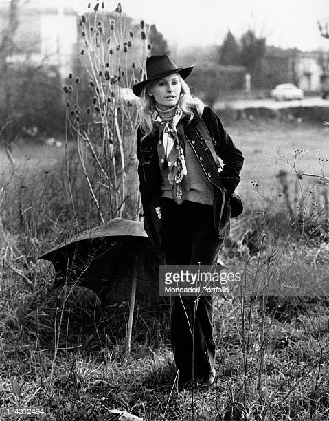 Italian television presenter and actress Gabriella Farinon walking in a field with her hand in her pocket Rome 1970s