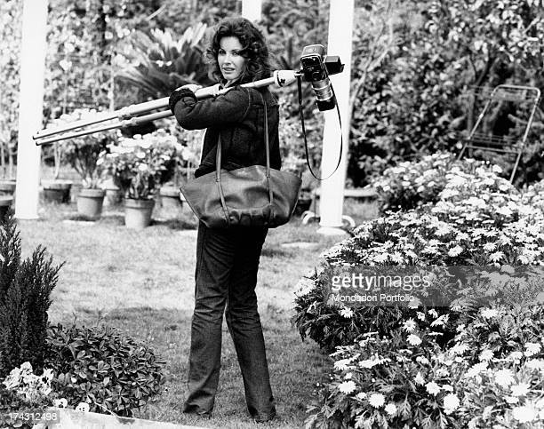 Italian television presenter and actress Gabriella Farinon walking in a garden with a camera with tripod on her shoulder Rome 1970s