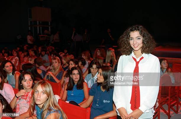 Italian television presenter and singer Ambra Angiolini smiling in the studio of the TV broadcast Non è la Rai wearing a red tie with the writing...