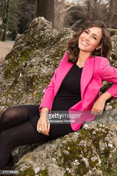 Italian television presenter Caterina Balivo posing smiling sitting on a rock at Giardini pubblici Indro Montanelli Milano 5th March 2013