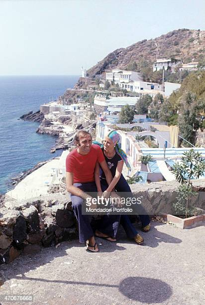 Italian television presenter Pippo Baudo and his wife Angela Lippi sitting smiling on a low wall Ustica 1972