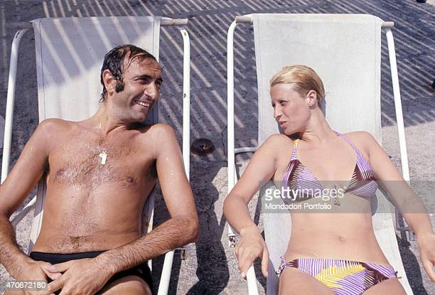 Italian television presenter Pippo Baudo sitting on a deckchair with his wife Angela Lippi Ustica 1972