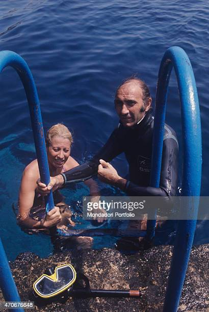 Italian television presenter Pippo Baudo wearing a diving suit going up a ladder with his wife Angela Lippi Ustica 1972