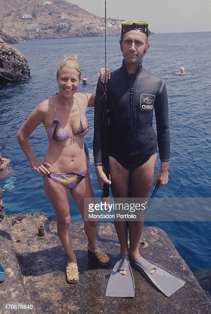 Italian television presenter Pippo Baudo wearing swim fins and a diving suit beside his wife Angela Lippi Ustica 1972