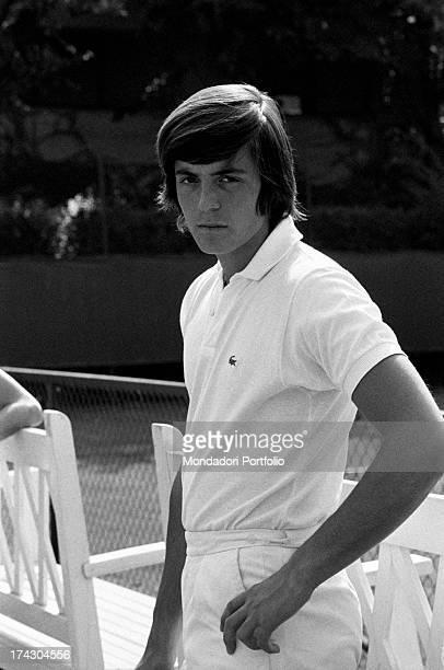 Italian tennis player Adriano Panatta holding his hand on his hip near a tennis court 1960s