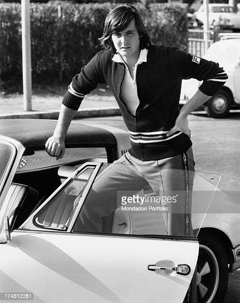 Italian tennis player Adriano Panatta posing leaning on a car Rome 1974