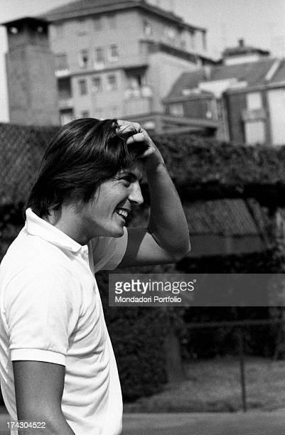 Italian tennis player Adriano Panatta smiling holding his hand among his hair 1960s