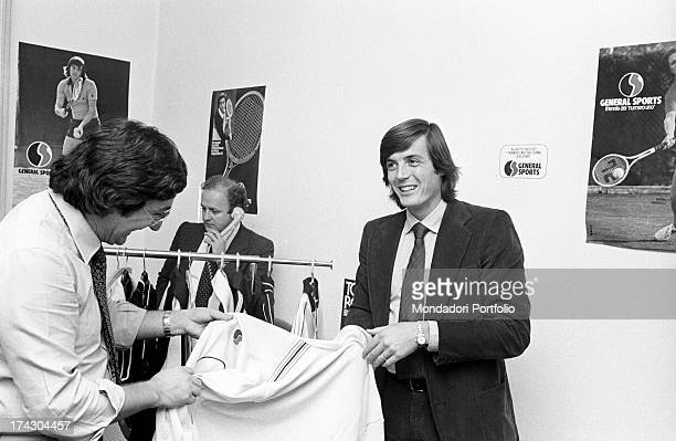 Italian tennis player Adriano Panatta smiling showing a sports jersey to a man 1970s