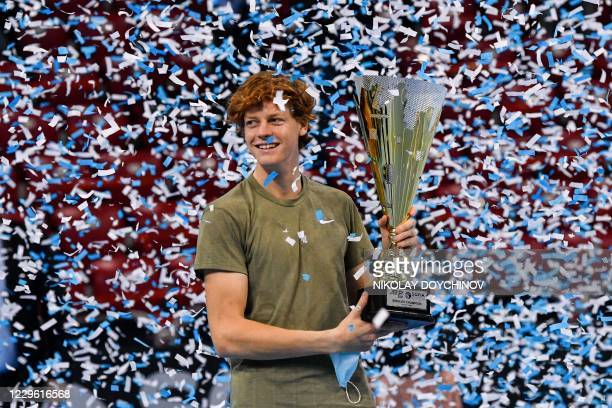 Italian tennis player Jannik Sinner celebrates with the trophy during the podium ceremony after winning the final against his Canadian opponent at...