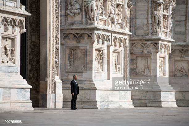 Italian tenor and opera singer Andrea Bocelli rehearses outside the Duomo cathedral on a deserted Piazza del Duomo in central Milan on April 12 prior...